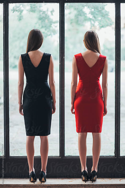 Two beautiful models in dresses standing near a window by Maja Topcagic for Stocksy United