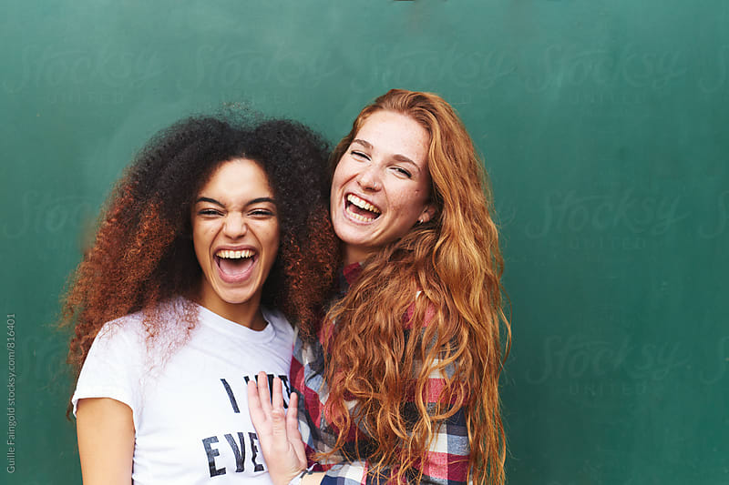 Portrait of two girlfriends laughing against of green background by Guille Faingold for Stocksy United