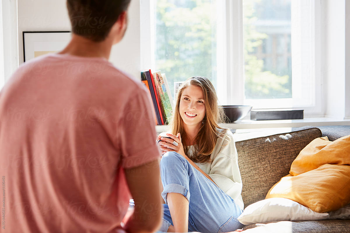 Happy Young Woman Talking With Man At Home by ALTO IMAGES - Couple, Talking