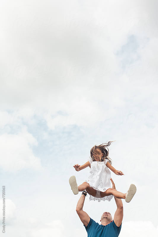 Man throwing little girl up in the air by Cindy Prins for Stocksy United