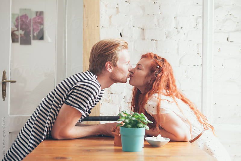 Caucasian Couple Kissing at a Cafe by Lumina for Stocksy United