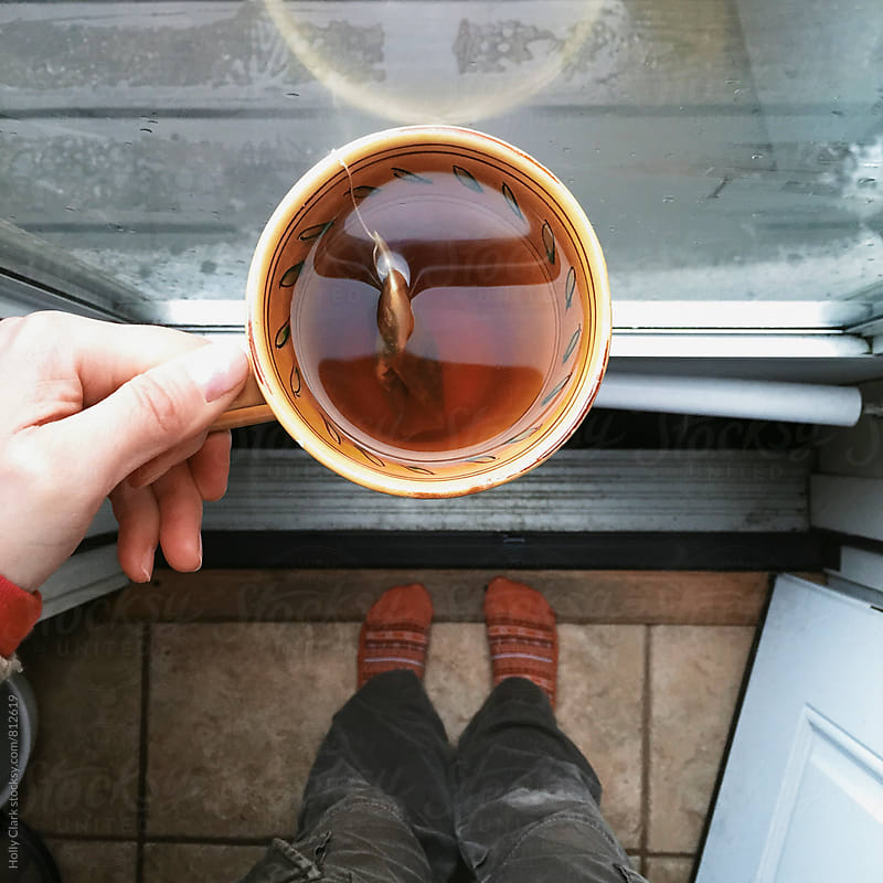 Cup of hot tea on a rainy day. by Holly Clark for Stocksy United