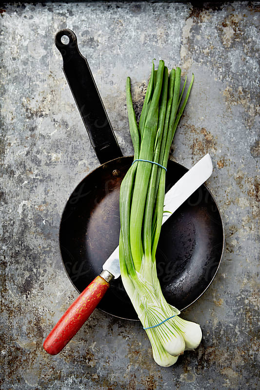 Spring onions in a pan with a knife by James Ross for Stocksy United