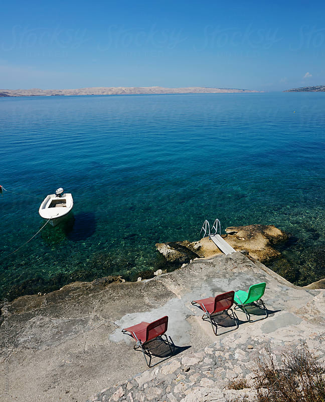Photo of a sea, boat and colorized chairs by Hamza Kulenović for Stocksy United