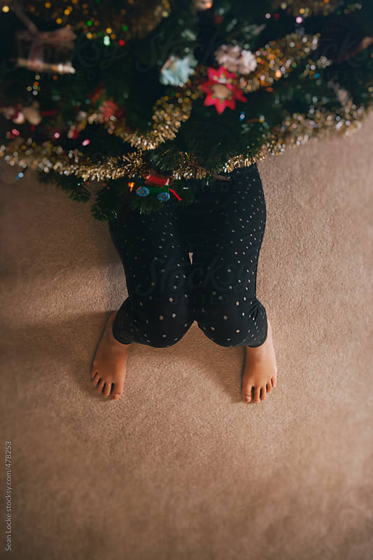 Pajamas: Woman Lies Under Christmas Tree With Feet Sticking Out by Sean Locke for Stocksy United