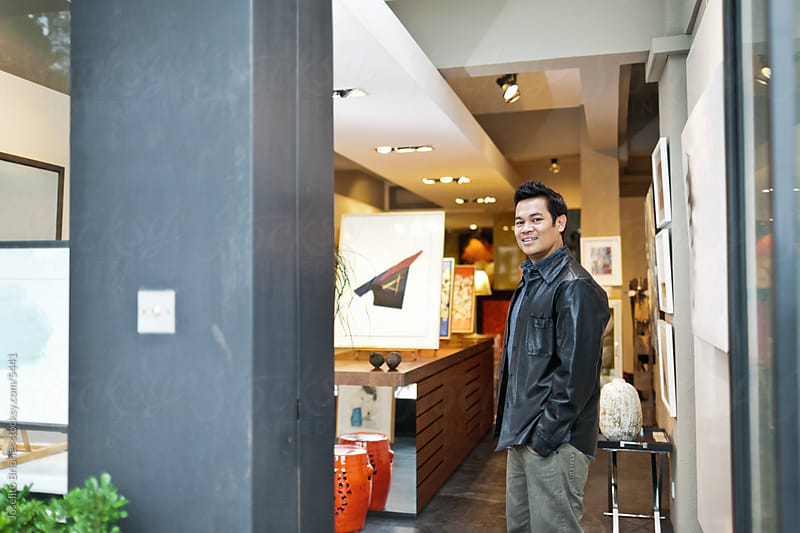 Small Art Gallery Business Owner Standing to Welcome Customers by Joselito Briones for Stocksy United