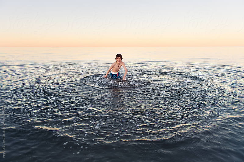 Happy child spinning circles into the surface of calm water at the beach by Angela Lumsden for Stocksy United