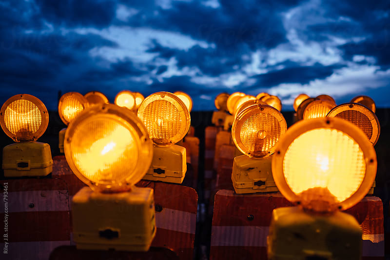 Two dozen illuminated, flashing road construction barricade signs in front of a dramatic sky. by Riley Joseph for Stocksy United