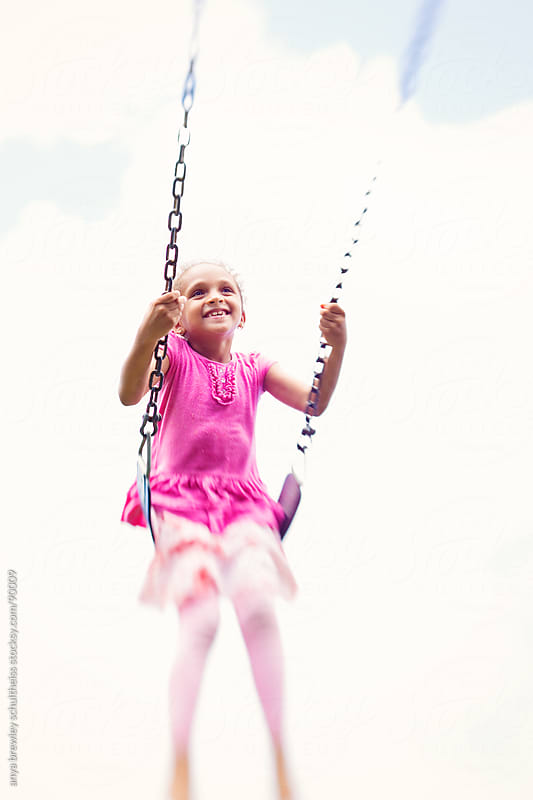 Portrait of young girl swinging freely and smiling happily by anya brewley schultheiss for Stocksy United