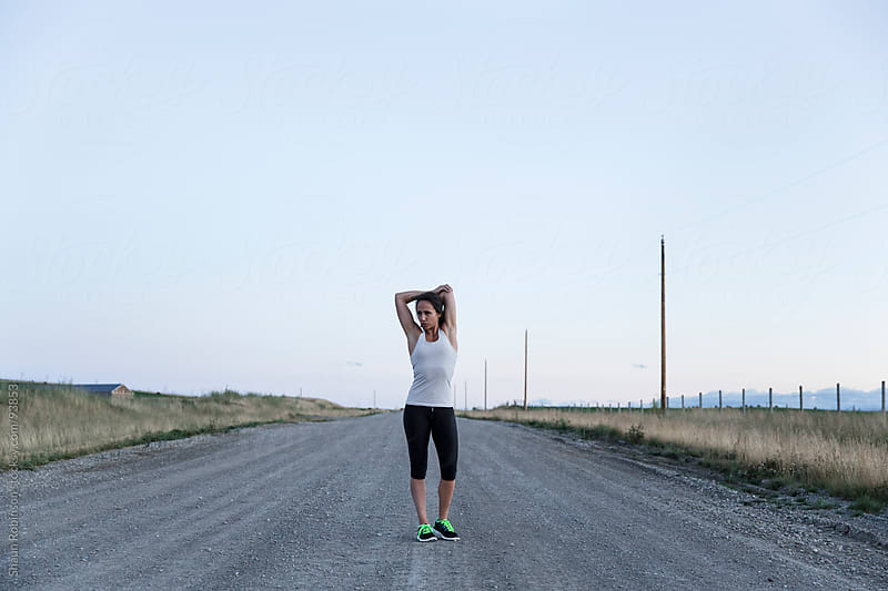A young fit woman stretching on a country road by Shaun Robinson for Stocksy United