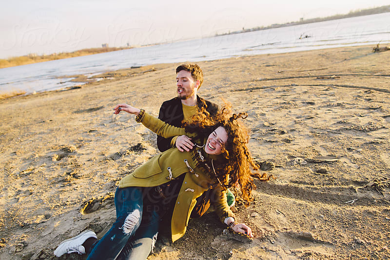 Young playful couple having fun on the sand  by Evgenij Yulkin for Stocksy United