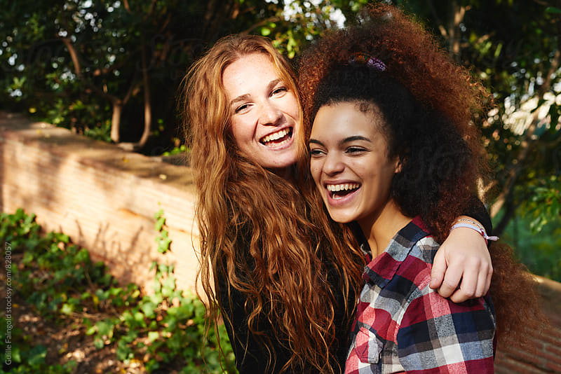 two young girlfriends laughing while hugging by Guille Faingold for Stocksy United