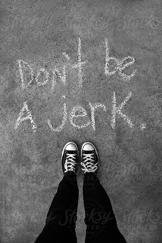 Person in black sneakers standing above chalk words saying - Don't be a jerk by Carolyn Lagattuta for Stocksy United