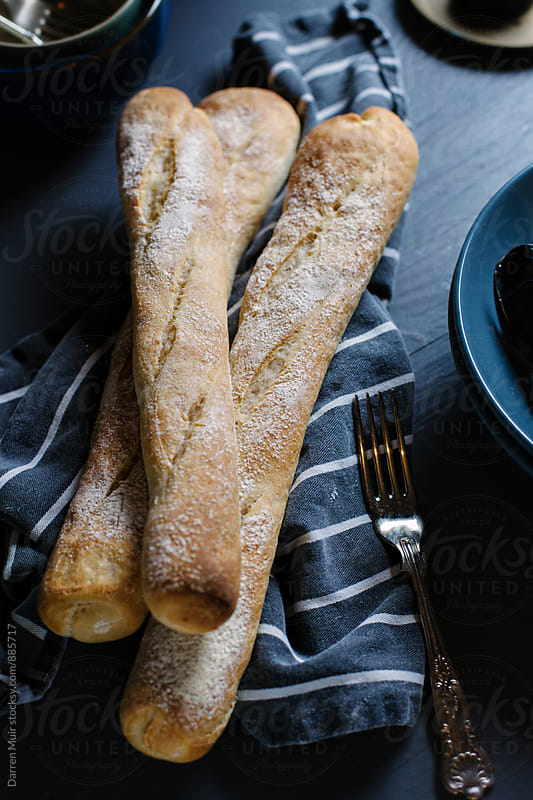 Freshly baked sticks of bread on a kitchen cloth. by Darren Muir for Stocksy United
