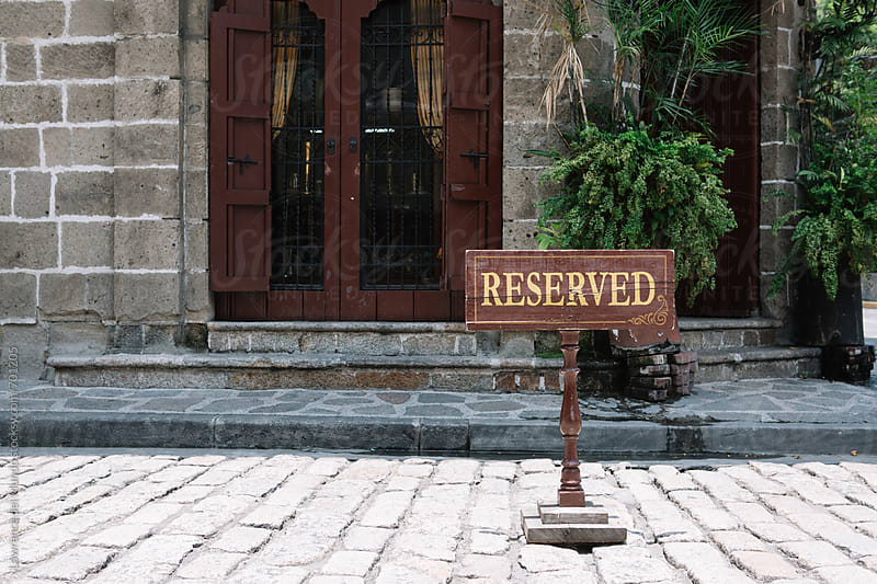 Reserved sign prominently displayed in front of a door entrance in an old town by Lawrence del Mundo for Stocksy United