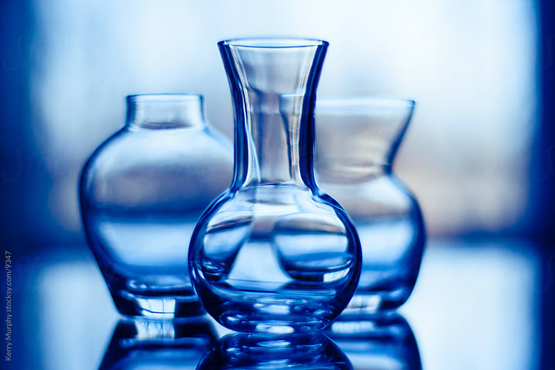 Glass vases still life in blue with window light by Kerry Murphy for Stocksy United