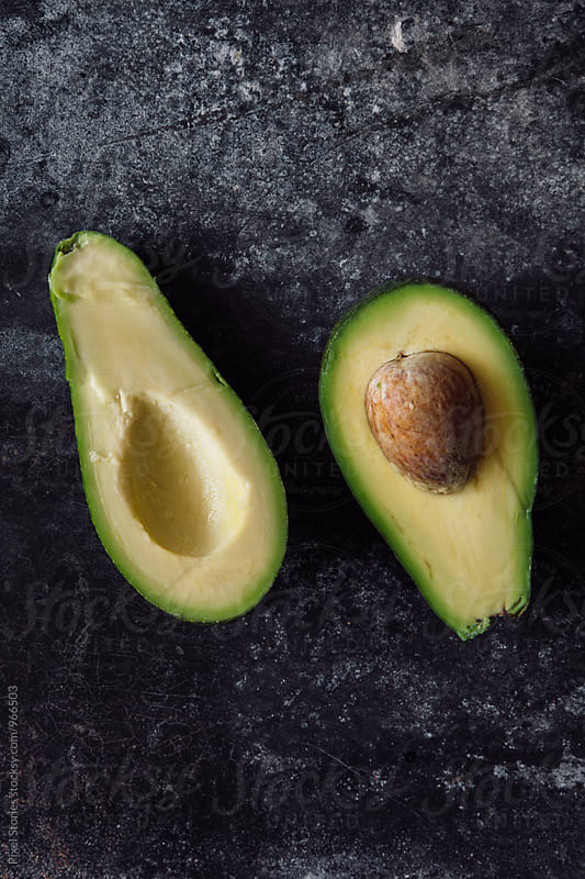 Ripe juicy avocado cut in half by Pixel Stories for Stocksy United