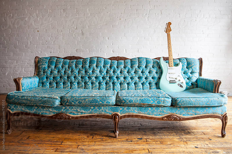 vintage blue couch with vintage blue guitar by Lisa MacIntosh for Stocksy United