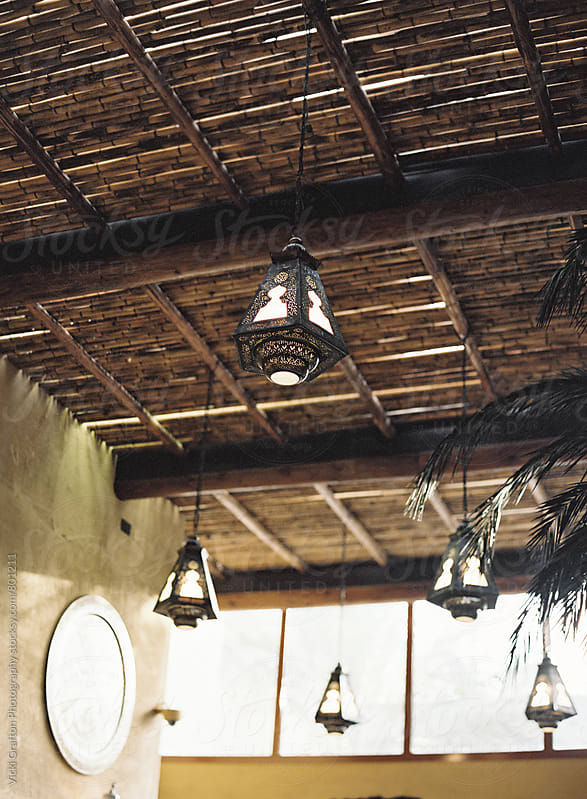 Hanging brass lanterns with thatched roof in the desert of Dubai by Vicki Grafton Photography for Stocksy United