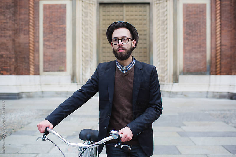 Portrait of young man walking with his bicycle by michela ravasio for Stocksy United