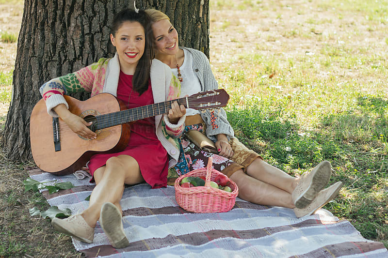 Woman playing guitar for her friend in nature by Evil Pixels  Photography for Stocksy United