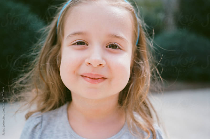 Close up portrait of a cute young girl with big cheeks by Jakob for Stocksy United