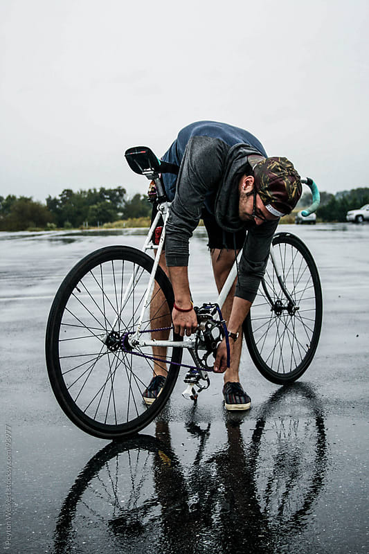 Hip young man fixed his bike in the rain by Peyton Weikert for Stocksy United