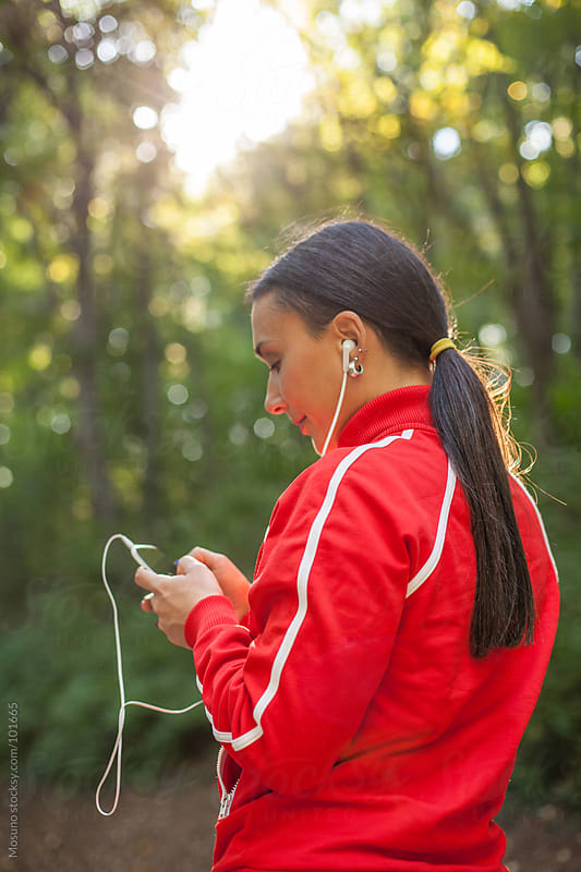 Female Runner Listening to Music in the Park by Mosuno for Stocksy United