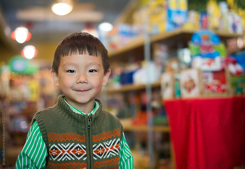 Smiling Asian Kid In a Toy Store by Brian McEntire for Stocksy United
