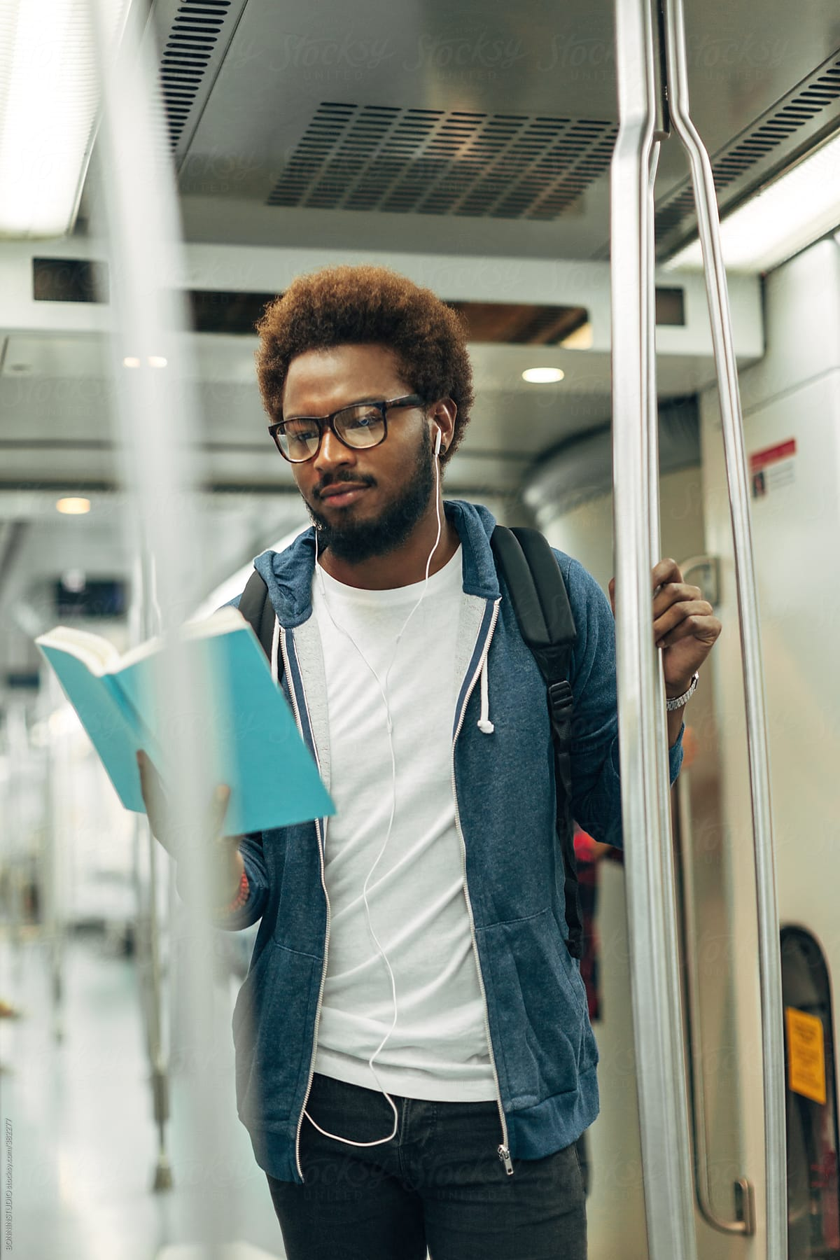 Afro Black Man Reading A Book On The Subway Train. by BONNINSTUDIO