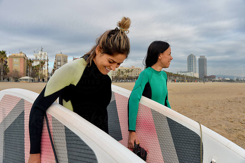 Two girlfriends with their paddle boards in Barcelona beach by Bisual Studio for Stocksy United