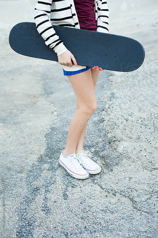 Teen girl holding her skateboard wearing shorts and sneakers by Carolyn Lagattuta for Stocksy United