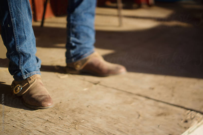 A free lens image of a man's cowboy boots on an old porch by Tana Teel for Stocksy United