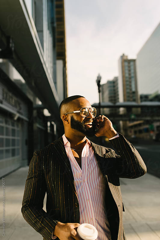 Man talking on smartphone while walking in Rosslyn, Va  by Cameron Whitman for Stocksy United