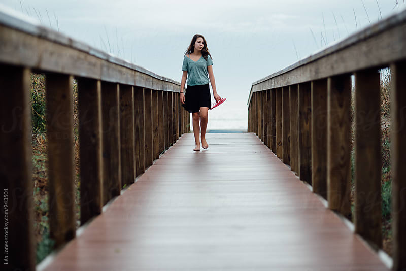 girl walking on boardwalk by Léa Jones for Stocksy United