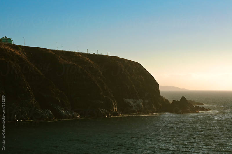 Sun shinning on a cliff in the Pacific Ocean by Constanza Caiceo for Stocksy United
