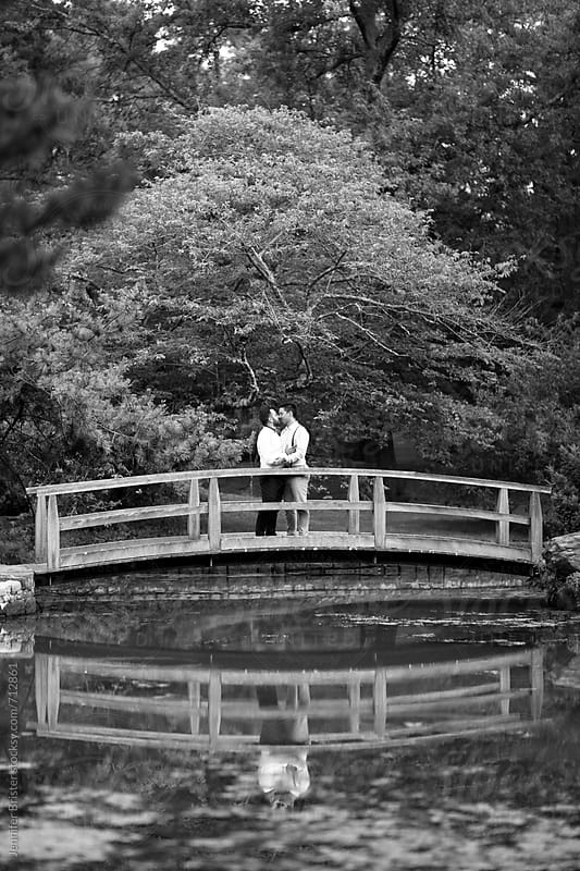 Couple kissing on bridge by Jen Brister for Stocksy United