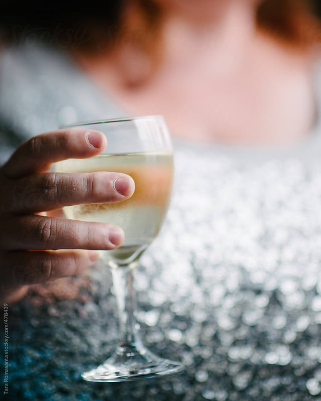 voluptuous woman holds a glass of white wine as if to toast by Tara Romasanta for Stocksy United