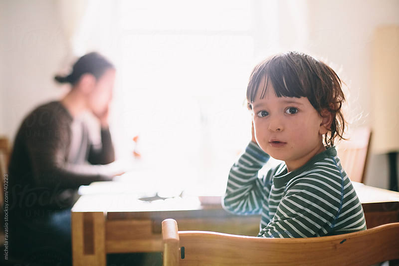 Child at the table with his father in background. by michela ravasio for Stocksy United