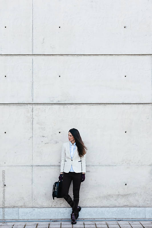 Young businesswoman standing on a big white wall.  by BONNINSTUDIO for Stocksy United