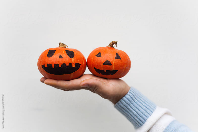 Male hand holding two small Halloween pumpkins in front of a white wall by VeaVea for Stocksy United
