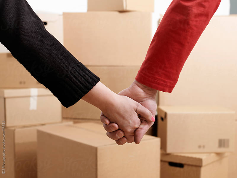 Couple holding hands surrounded by moving boxes by IDS Photography for Stocksy United