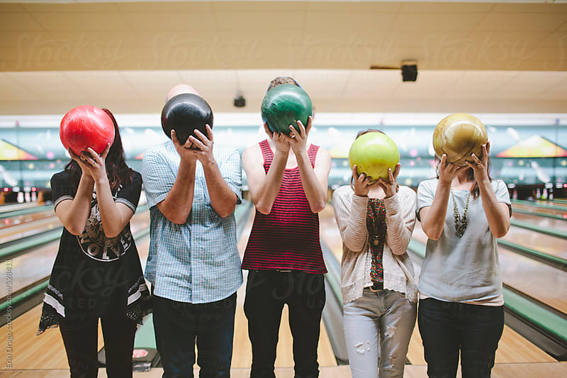 family with bowling balls in front of their faces by Erin Drago for Stocksy United