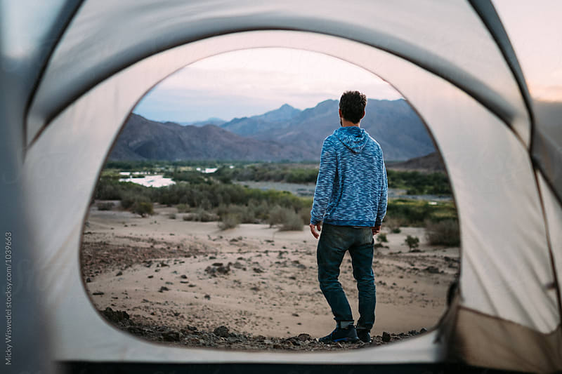 hiker standing outside his tent enjoying a desert view at dawn by Micky Wiswedel for Stocksy United