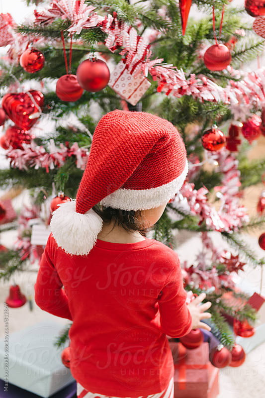 A cute toddler girl decorating christmas tree by Maa Hoo for Stocksy United