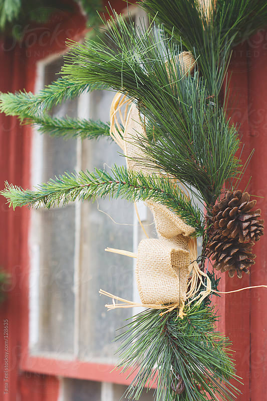 A rustic evergreen hangs from an old window for the holiday season by Tana Teel for Stocksy United