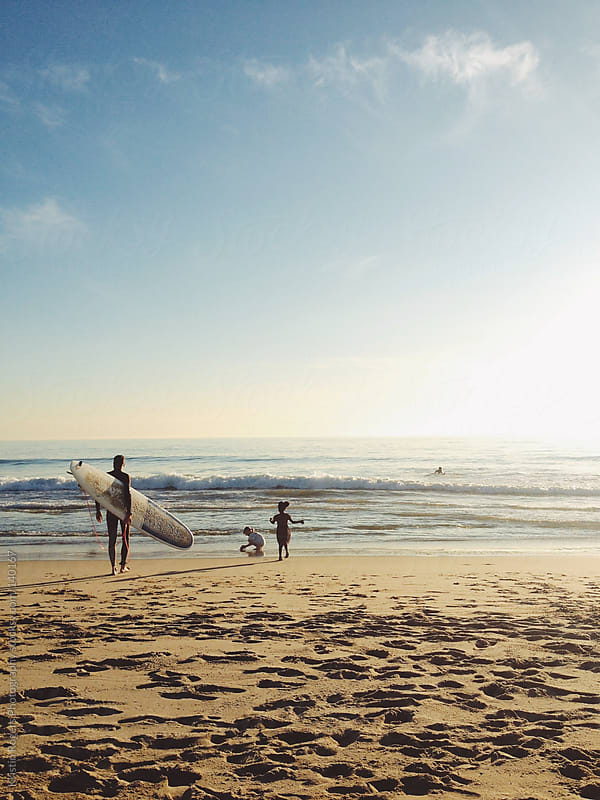 Father going into ocean to surf with children playing on sand by Kristin Rogers Photography for Stocksy United