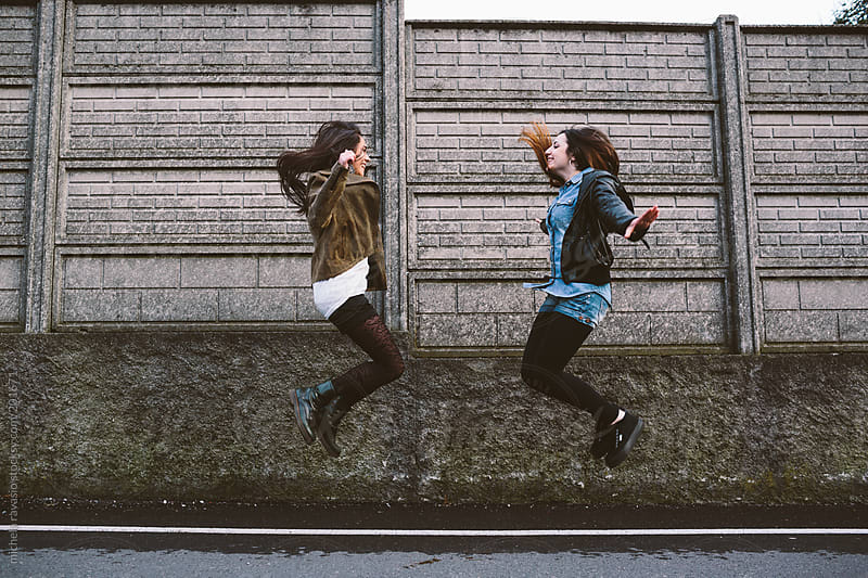 Teenage girls jumping together by michela ravasio for Stocksy United