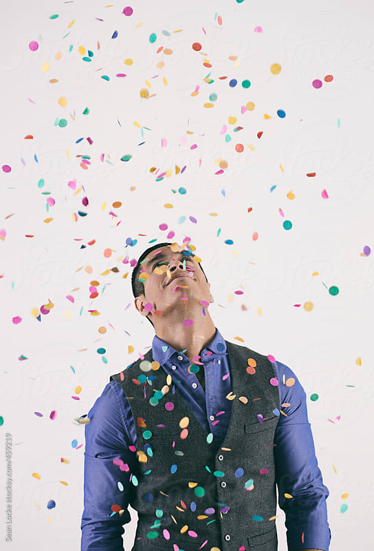 Holiday: Man Looks Up Into Confetti Storm by Sean Locke for Stocksy United
