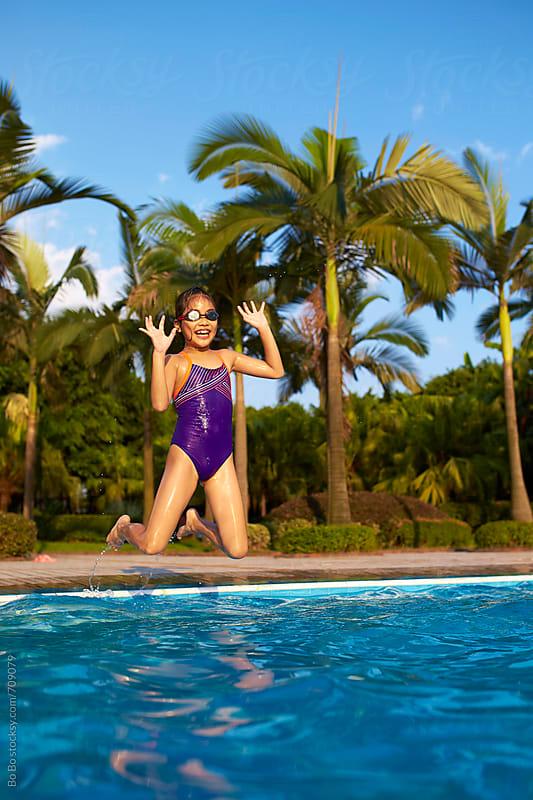 lovely little asian girl having fun in swimming pool by Bo Bo for Stocksy United